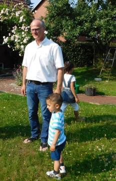 Diakon Wille und die Kinder im Garten eines Nachbarn der syrischen Familie.