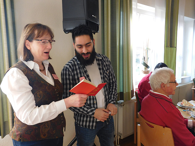 """Gemeinsames deutsch-arabisches Singen des Lieds """"Der Himmel geht über allen auf"""". Die Flüchtlinge wissen, zu Agnes können wir immer gehen, sagte Franz Huchtkemper über die engagierte Helferin Agnes Droste."""