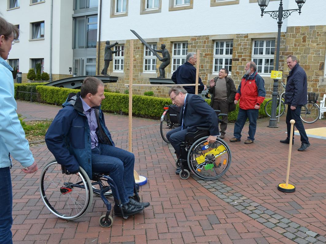 Hubert Meyer (Bildmitte in der braunen Jacke) während seiner Zeit als Behindertenbeauftragte. Auch Samtgemeindebürhermeister Horst Baier erlebte, was schon kleinste Barrieren für Rollstuhlfahrer bedeuten. Foto: Samtgemeinde Bersenbrück.